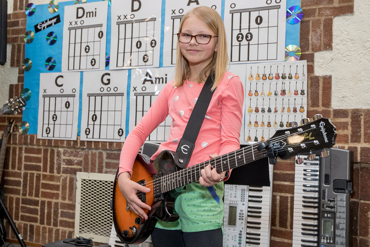girl playing electric guitar